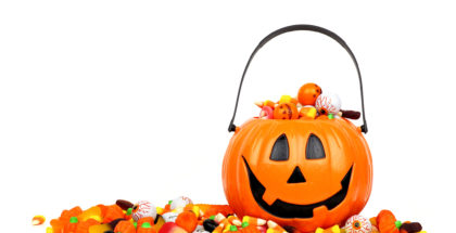 Halloween Jack o Lantern bucket filled with candy isolated on white