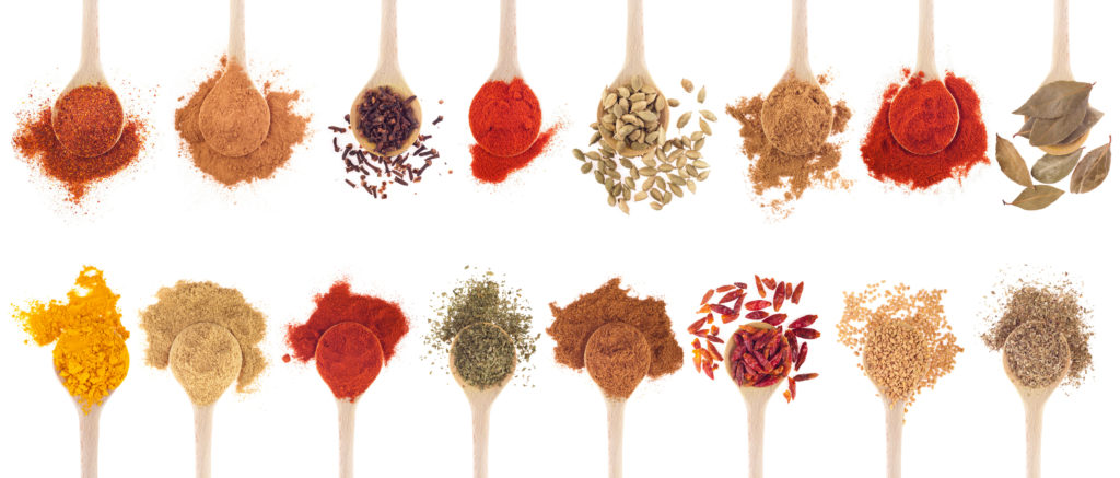 A collection of different spices on wooden spoons